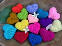 Falling flower and leaf on colourful hearts in wooden tray in the garden Stock Image