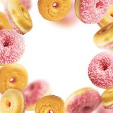 Falling or flying pink glazed doughnuts with sprinkles in motion at withe background. Frame Stock Photos