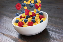Falling fresh berries in corn flakes Royalty Free Stock Image