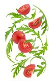 Falling fresh vegetables. Cherry tomatoes and rucola isolated on white background. With clipping path Stock Image