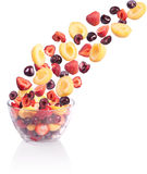 Falling fruit in a glass bowl. Isolated on white Stock Photos