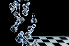 Falling Glass Chess Pieces. On a Glass Chess Board Stock Photos