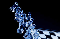 Falling Glass Chess Pieces. On a Glass Chess Board Royalty Free Stock Photo