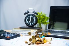 Falling gold coin, flying coin or rain money on working table with office supplies or office work essential tools items for. Business financial concept idea stock photo