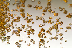 Falling gold crystals. On gradient background Stock Image