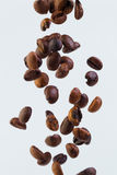Falling grains of roasted coffee on a white background Stock Photos