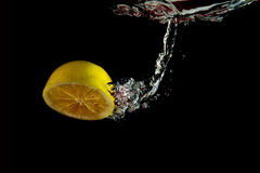 Falling half of lemon into water Stock Photography