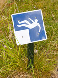 Falling hazard sign. Blue falling hazard sign standing in the grass royalty free stock photography