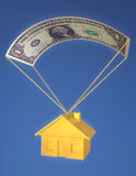 Falling Home Prices. A golden house falling from the sky with a dollar bill parachute, against a blue sky. Symbol of falling home prices, investment risk, or a Stock Photos