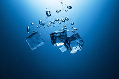 Falling ice cubes in water Royalty Free Stock Photography