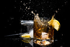 Falling of ice in glass of whiskey and makes many splashes and another glass lying on side with lemon slice inside, tubules and ic Royalty Free Stock Photography