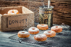 Falling icing sugar on fresh donuts. On old wooden table Stock Photos