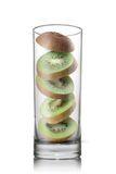 Falling kiwi slices inside glass isolated Stock Photography