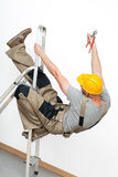 Falling from ladder. A worker with a yellow helmet falling from a metal ladder Stock Photos