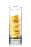 Falling lemon slices inside glass isolated Stock Image