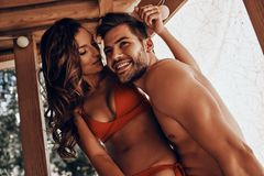 Falling in love?. Beautiful young couple embracing and smiling while resting in the beach hut royalty free stock photo
