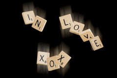 Falling In love (black background). Falling scrabble pieces spelling the words in love XOX stock photo