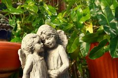 Falling in love. Closeup of two angel lover statues standing together in the garden, love concept royalty free stock image