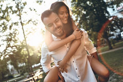 Falling in love. Handsome young men carrying young attractive women on shoulders while spending time together outdoors royalty free stock images
