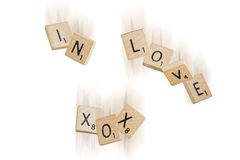 Falling In Love (white background). Falling scrabble pieces spelling the words in love XOX stock images