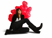 Falling in love, woman sitting on white background. A young woman is sitting on the ground looking up. Behind her there are some lovely red balloons in the shape Royalty Free Stock Photo