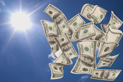 Falling money $100 bills. With blue sky and sun as background Stock Photography