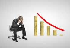 Falling money graph. Sad businessman sitting on chair with falling money graph Stock Photo