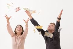 Falling Money. Young couple catching falling money Stock Image