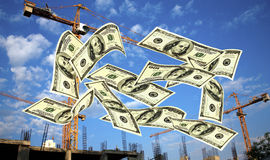 Falling notes of US dollar against cranes Stock Photography