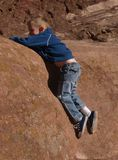 Falling Off The Rocks. A color image of a young boy sliding of of red rocks Royalty Free Stock Photography