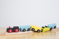 Falling off the tracks - Failure concept. Derailed toy train - Conceptual image failure, out of control Royalty Free Stock Images
