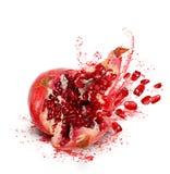 Falling pomegranate with splashes of juice Stock Photos