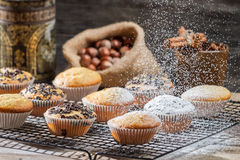Falling powder sugar on vanilla muffins. On old wooden table Stock Image