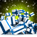Falling presents. With blue ribbon over a bright snowy  green background Stock Images