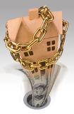 Falling property values. An unstable economy with falling property prices is illustrated by a chained up house and money being flushed down the drain royalty free stock image