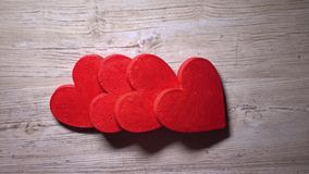 Falling red hearts, domino effect, top view. Consequences and chain reaction concepts. 4K video. Falling red hearts, domino effect, top view. Consequences and stock footage