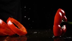 Falling red paprika cuts with water splash, slow motion stock video