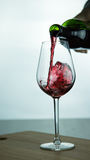 Falling red wine in glass. Falling red wine in a glass on wood surface Royalty Free Stock Photos