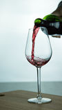 Falling red wine in glass. Falling red wine in a glass on wood surface Stock Photos