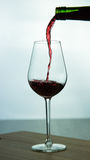 Falling red wine in glass. Falling red wine in a glass on wood surface Royalty Free Stock Image