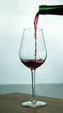 Falling red wine in glass. Falling red wine in a glass on wood surface Royalty Free Stock Images
