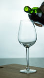 Falling red wine in glass. Falling red wine in a glass on wood surface Royalty Free Stock Photo