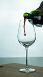 Falling red wine in glass. Falling red wine in a glass on wood surface Stock Photo