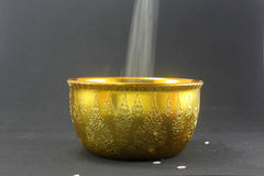 Falling Rice in the Traditional Thai golden bowl Stock Images