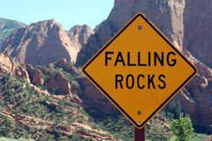Falling rocks ahead road sign. Falling rocks road sign and mountains royalty free stock photography