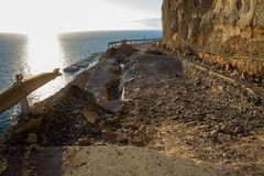 Falling rocks and big collapse hole on closed mountain road under the sea.  stock photos