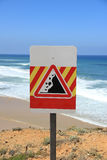 Danger falling rocks sign near a beach Stock Photo