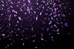 Falling Shiny Glitter purple Confetti isolated on black background. Christmas or Happy New Year Confetti. Royalty Free Stock Photo
