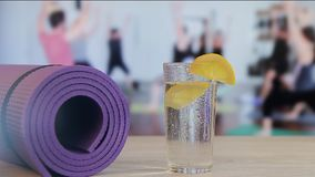 Falling of a slice of a lemon in a glass with water, yoga, pilates, group employment by sports