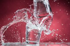Falling small glasses and spilling water on a blue background. Falling small glasses and spilling water on a red background royalty free stock images